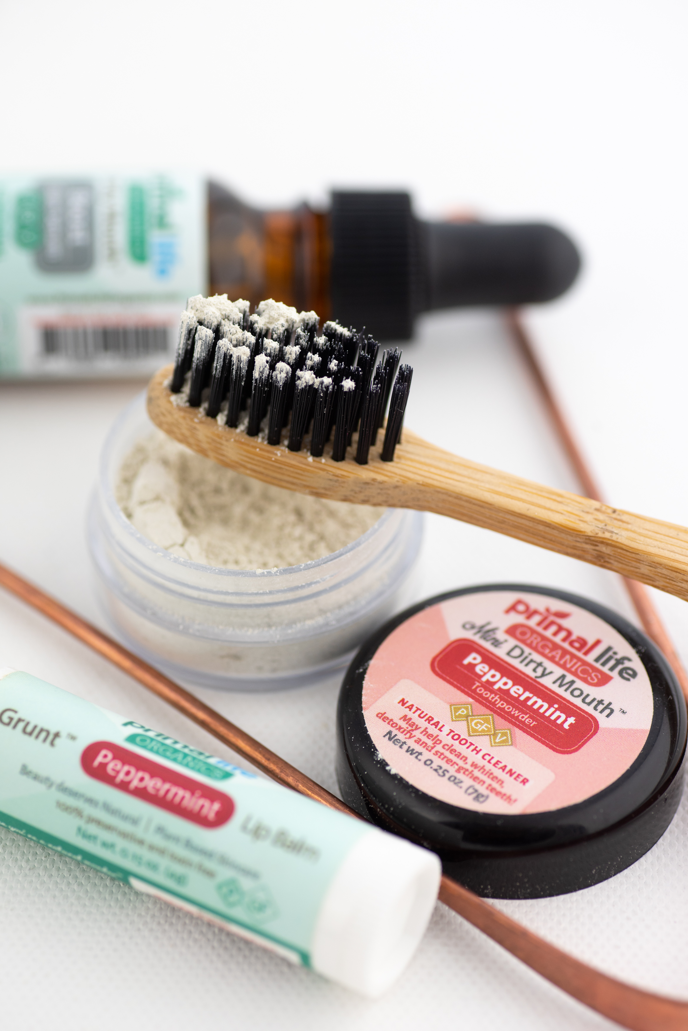 Close-up of Dental Starter Kit, focusing on Dirty Mouth Toothpowder on charcoal ion toothbrush